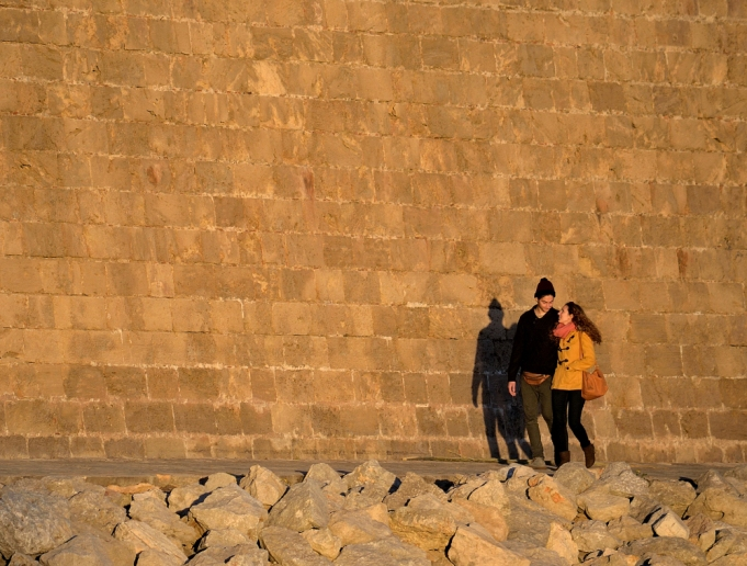 couple walking beneath very high walls