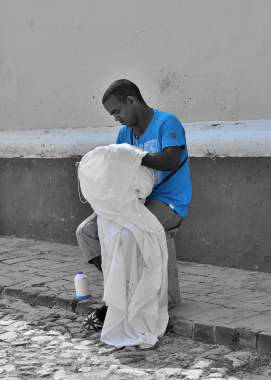 man in bright blue t-shirt sewing a white cloth