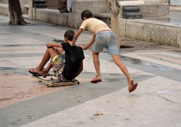 view from behind of boy pushing another boy on home made skate board