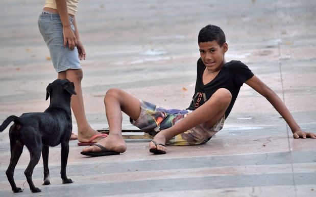 Boy sitting on the ground with dog beside him.