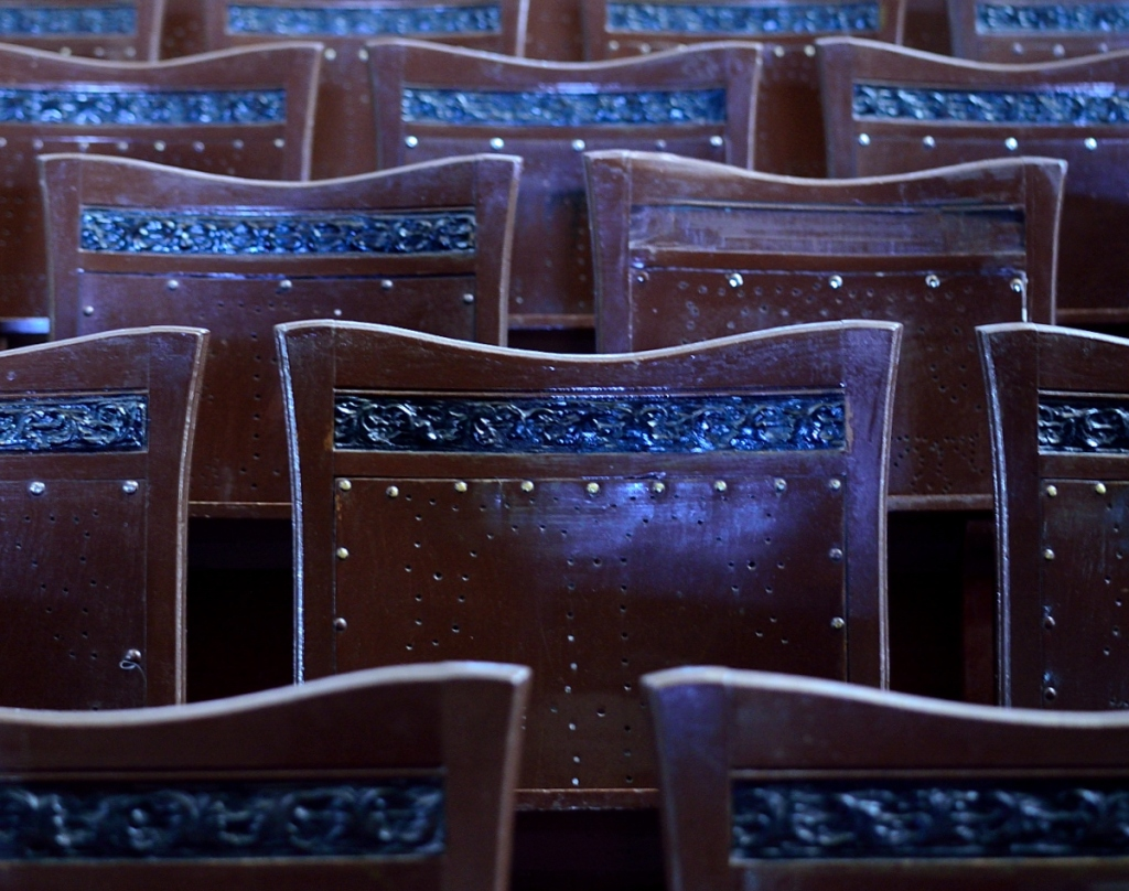 the backs of theatre seats. with decorative strip missing from one.