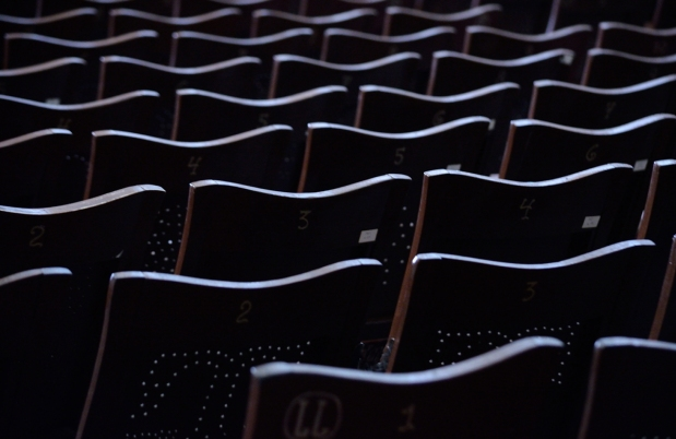 row of seats from behind with tops of seats highlighted and the rest dark.