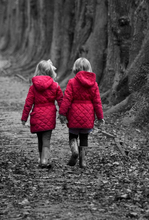 two little girls in B&W with their coats recoloured red.